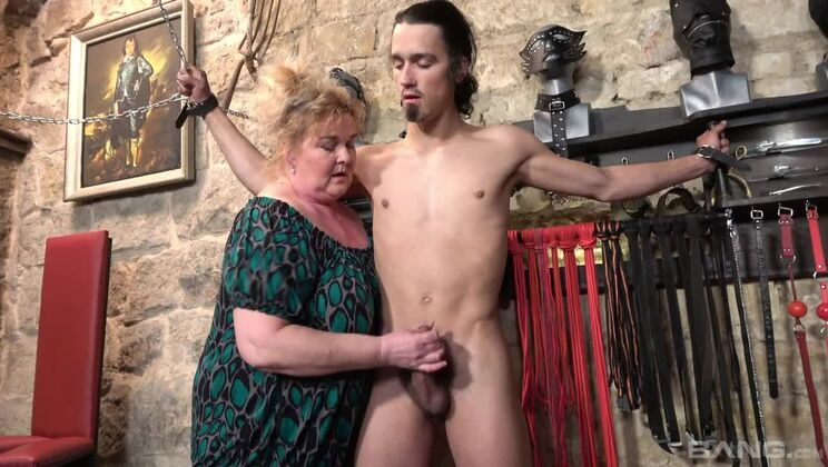 BDSM granny chains college hunk to the wall and plays with his cock!